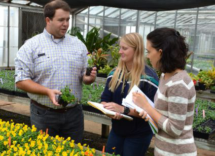Dr. Barnes with students in greenhouse