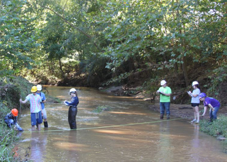 students measuring a stream